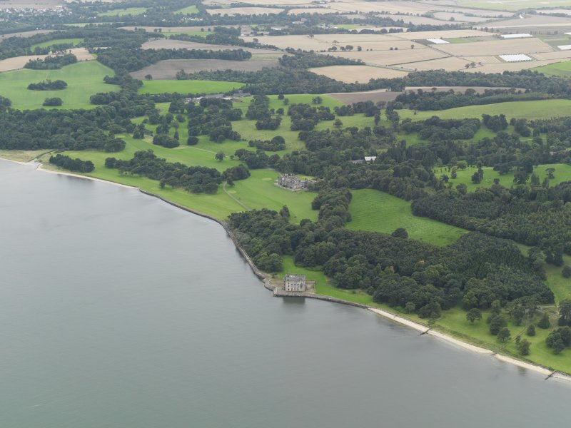General oblique aerial view centred on the country house with Barnbougle Castle adjacent, taken from the NW.