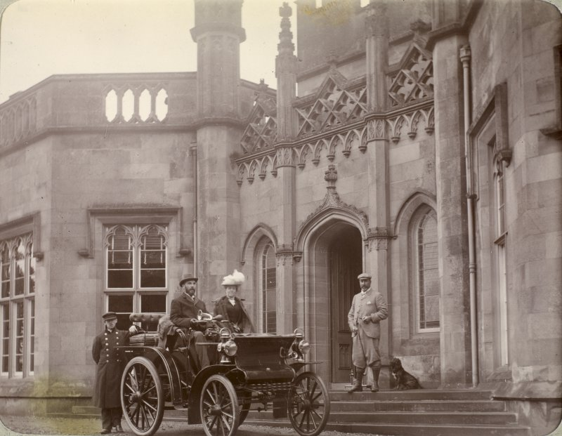 View of Inchrye Abbey entrance with couple in automobile.