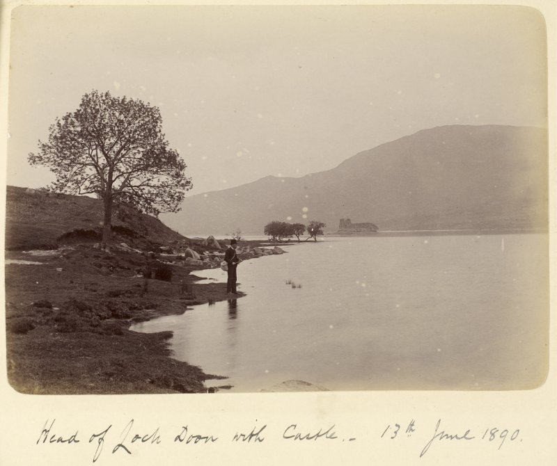 View of man fishing with the castle in the background.  Titled: 'Head of Loch Doon with Castle. 13th June 1890'.