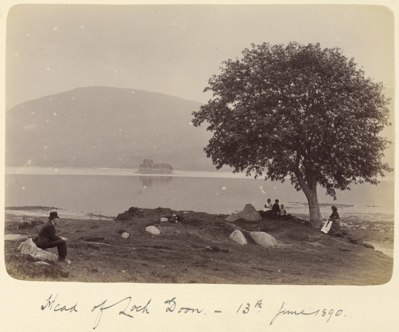 View of family group at lochside with castle in the background. Titled: 'Head of Loch Doon. 13th June 1890'.