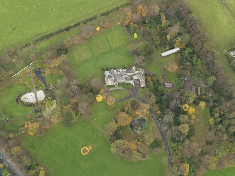 Oblique aerial view centred on castle with the policies adjacent, taken from the SSW.