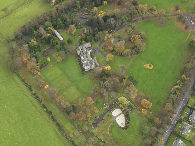 Oblique aerial view centred on castle with the policies adjacent, taken from the  WNW.