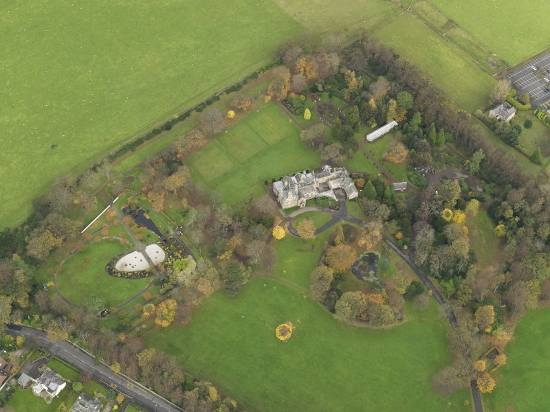 Oblique aerial view centred on castle with the policies adjacent, taken from the  SW.