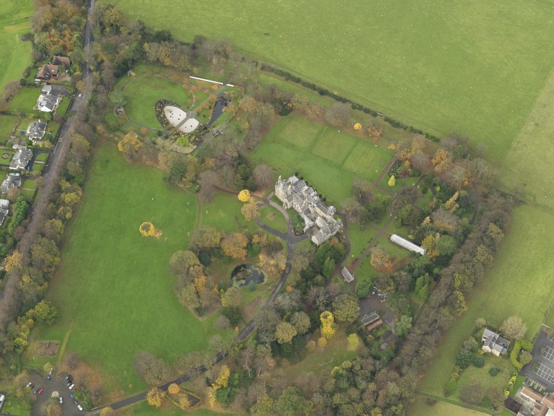Oblique aerial view centred on castle with the policies adjacent, taken from the  SE.