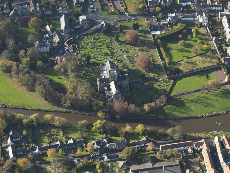 Oblique aerial view centred on the church with the grayeyard adjacent, taken from the ENE.