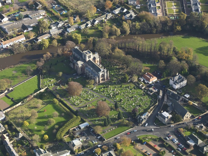 Oblique aerial view centred on the church with the grayeyard adjacent, taken from the NW.