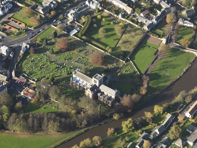 Oblique aerial view centred on the church with the grayeyard adjacent, taken from the SE.