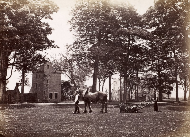 View of Wemyss Castle grounds near the gatehouse with a horse-drawn grass cutter in operation in the foreground.