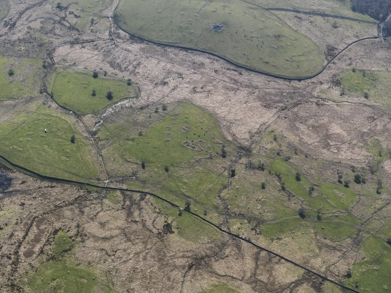 Oblique aerial view of the remains of the field-systems, rig, small cairns, cairn and farmstead at the Moor of Barclye, taken from the NE.