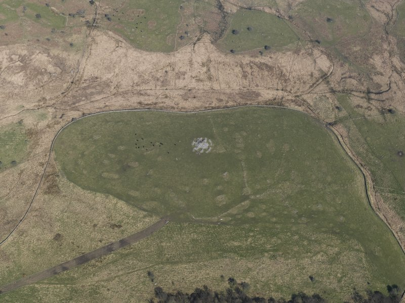 Oblique aerial view of the remains of the field-systems and cairn at Drumwhirn, taken from the SW.