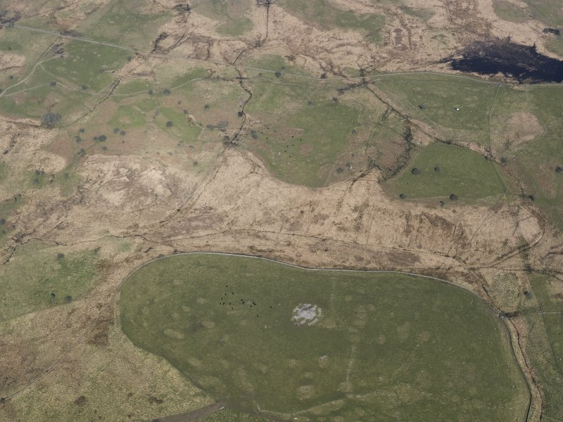 Oblique aerial view of the remains of the field-systems, rig, small cairns and farmstead at the Moor of Barclye, taken from the NNE.
