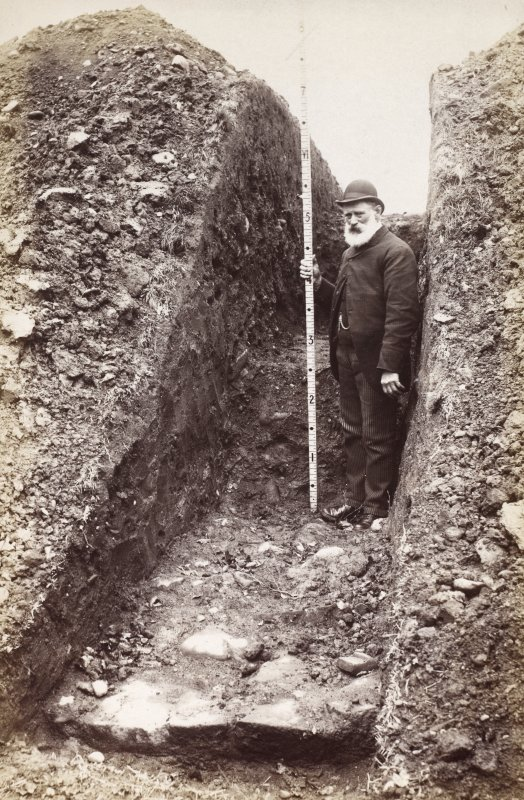 Photograph of south west rampart excavation trench at Ardoch Roman Fort, showing rough stone paving. Society of Antiquaries of Scotland excavations, 1896-7.