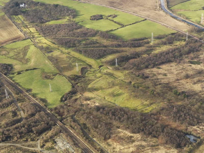 Oblique aerial view centred on the remains of Rough Castle Roman fort and the course of the Antonine Wall, taken from the SSE.