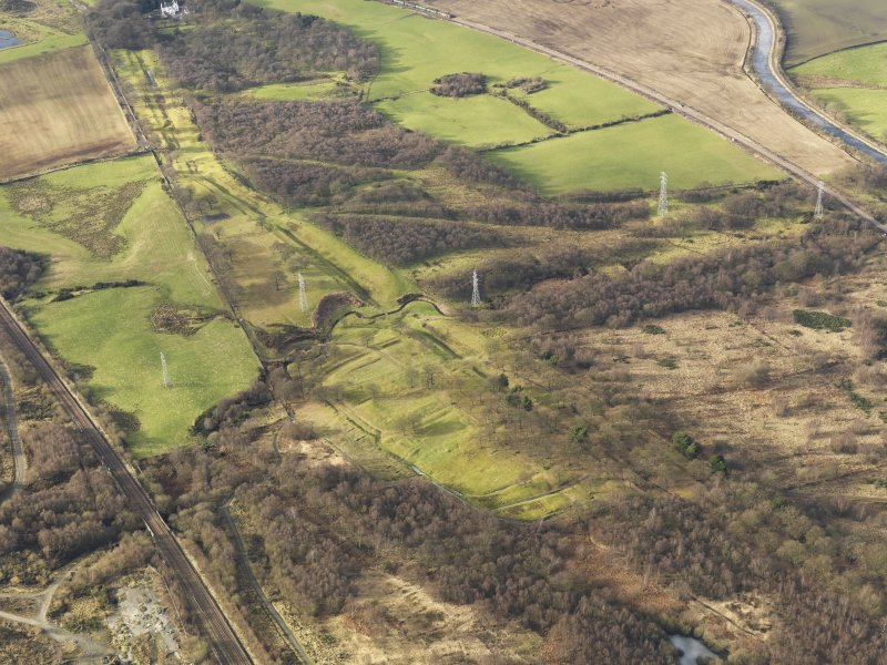 Oblique aerial view centred on the remains of Rough Castle Roman fort and the course of the Antonine Wall, taken from the ESE.
