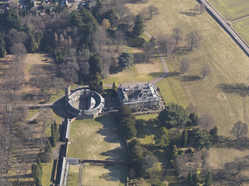 Oblique aerial view centred on the country house with the stable block adjacent, taken from the W.