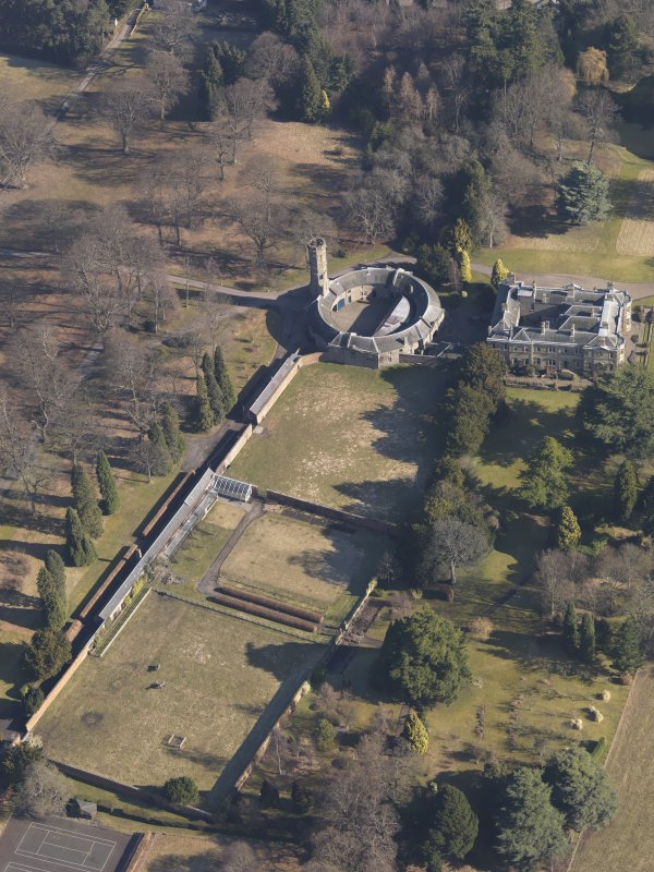 Oblique aerial view centred on the country house with the stable block and walled garden adjacent, taken from the SW.