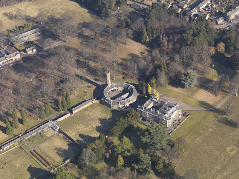 Oblique aerial view centred on the country house with the stable block adjacent, taken from the SW.