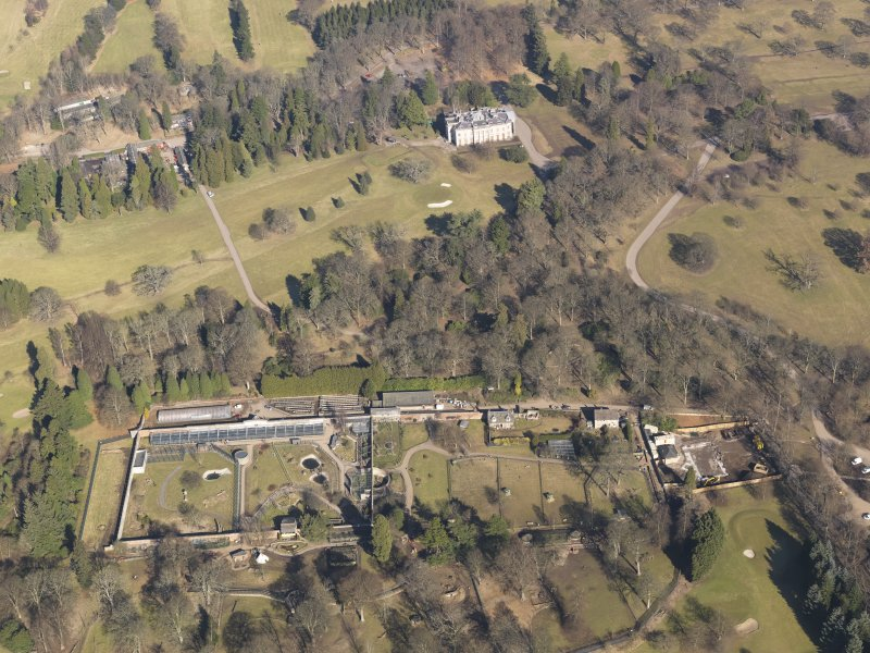 Oblique aerial view centred on the walled garden with the country house adjacent, taken from the  S.