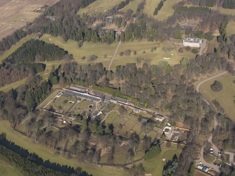 Oblique aerial view centred on the walled garden with the country house adjacent, taken from the  SSE.