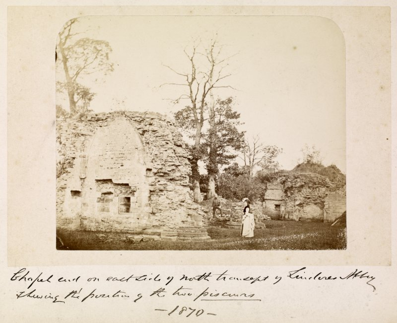 View of abbey with two people. Titled: 'Chapel end on east side of north transept, Lindores Abbey showing the portion of the two piscurns. 1870'.