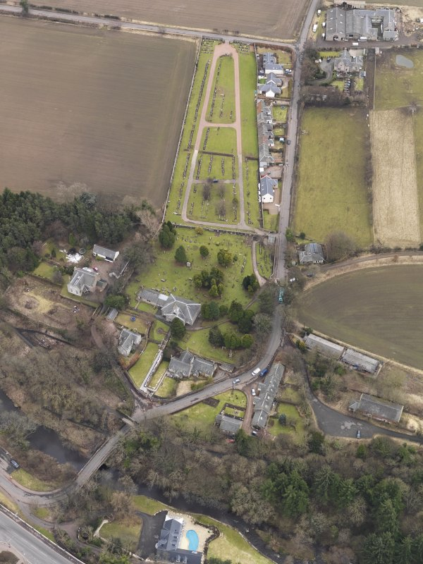 Oblique aerial view centred on the kirk with the burial ground adjacent, taken from the NW.