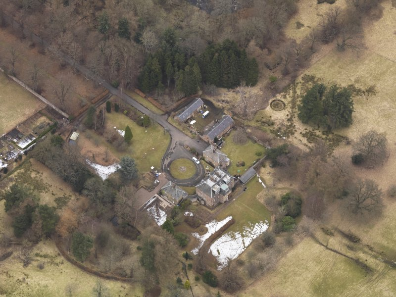 Oblique aerial view centred on the country house with the stable block, taken from the SSW.