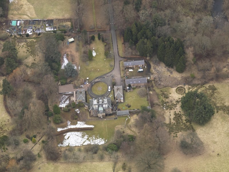 Oblique aerial view centred on the country house with the stable block, taken from the SSE.