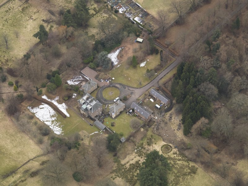 Oblique aerial view centred on the country house with the stable block, taken from the SE.
