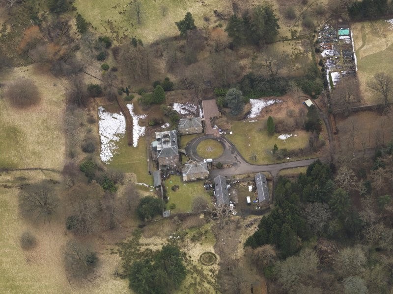 Oblique aerial view centred on the country house with the stable block, taken from the NE.