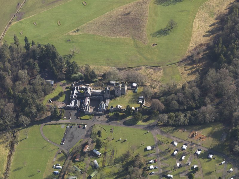 Oblique aerial view centred on the country house with the caravan park adjacent, taken from the W.