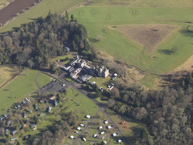 Oblique aerial view centred on the country house with the caravan park adjacent, taken from the SW.