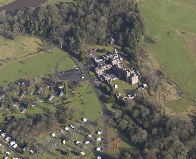Oblique aerial view centred on the country house with the caravan park adjacent, taken from the SSW.