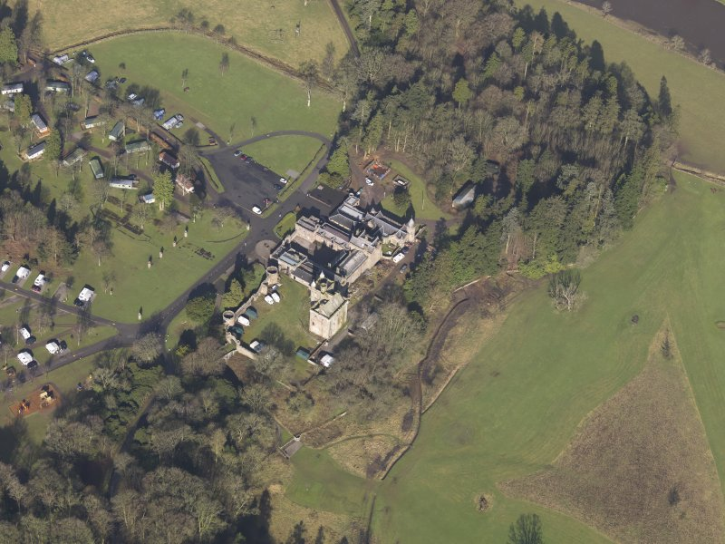 Oblique aerial view centred on the country house with the caravan park adjacent, taken from the SE.
