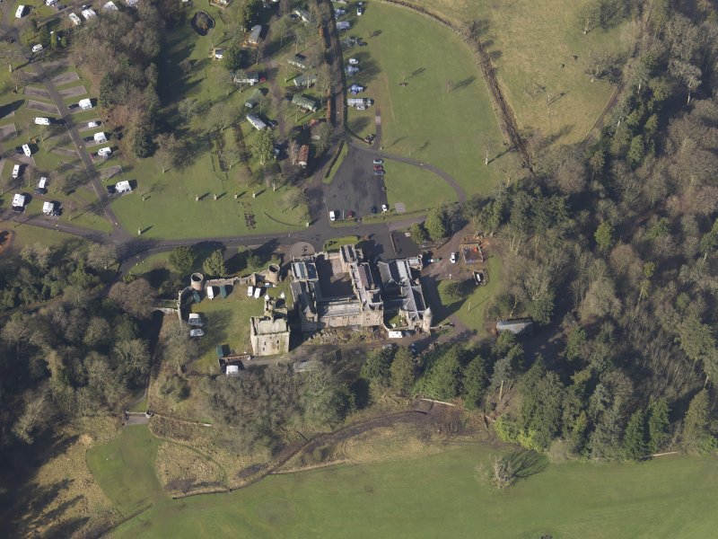 Oblique aerial view centred on the country house with the caravan park adjacent, taken from the E.
