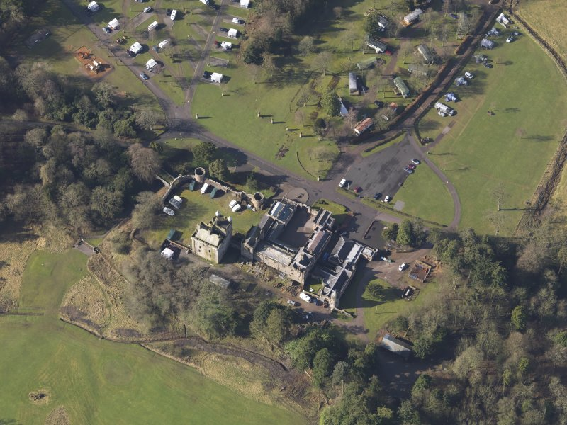 Oblique aerial view centred on the country house with the caravan park adjacent, taken from the NE.