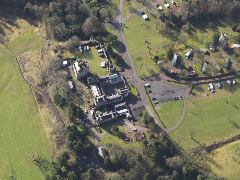 Oblique aerial view centred on the country house with the caravan park adjacent, taken from the N.