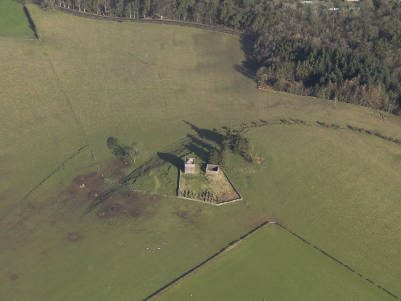 Oblique aerial view centred on the ruins of the tower house with the chapel and the graveyard adjacent, taken from the SSE.