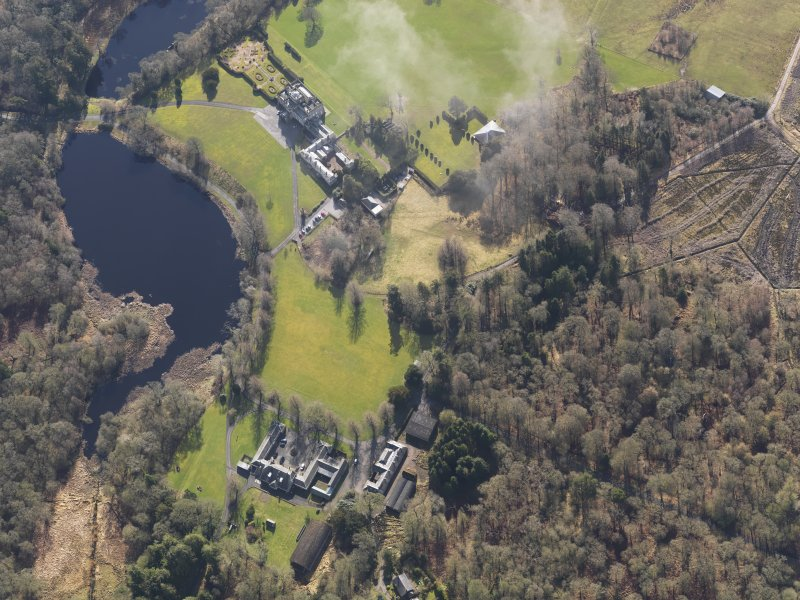 General oblique aerial view centred on the country house with the stables adjacent, taken from the NW.