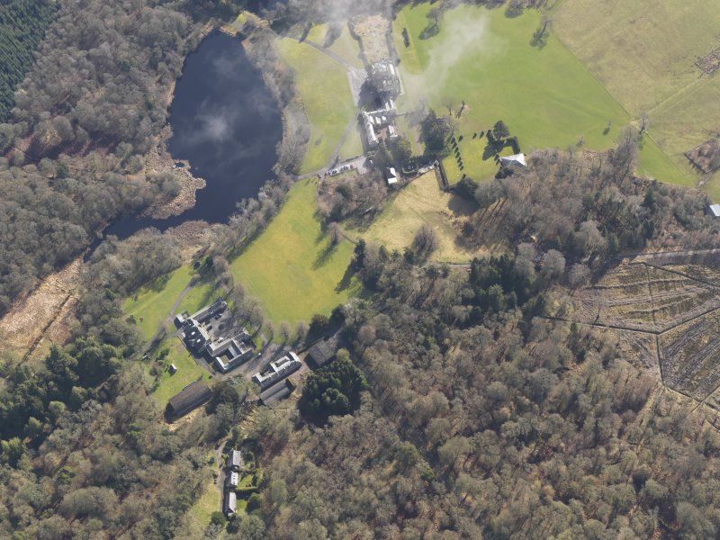 General oblique aerial view centred on the country house with the stables adjacent, taken from the WNW.