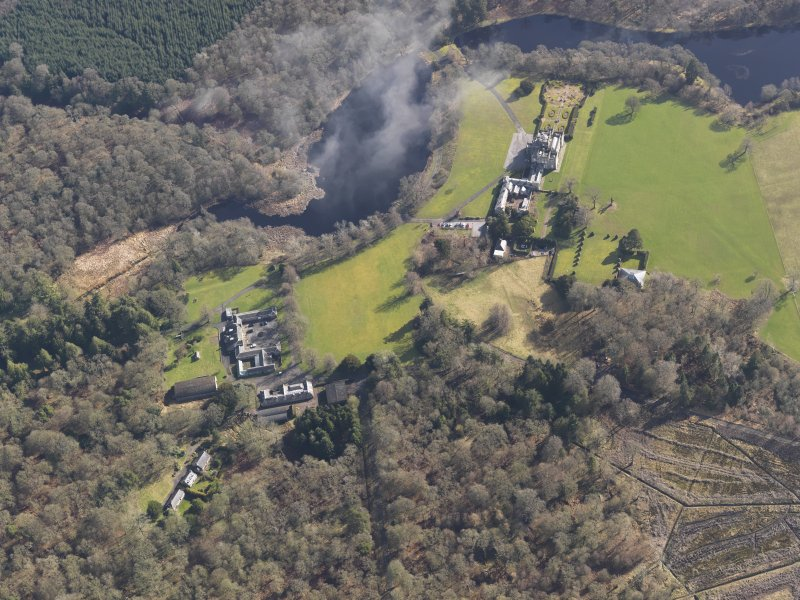 General oblique aerial view centred on the country house with the stables adjacent, taken from the W.