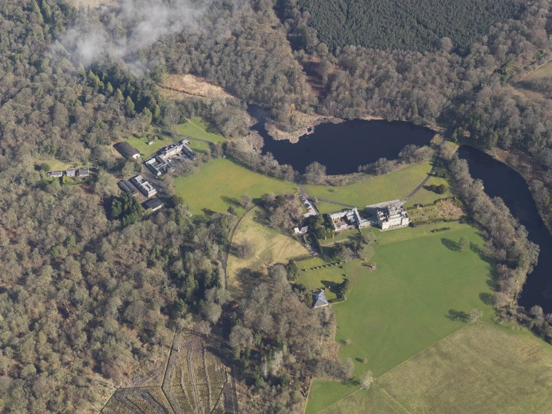 General oblique aerial view centred on the country house with the stables adjacent, taken from the SSW.