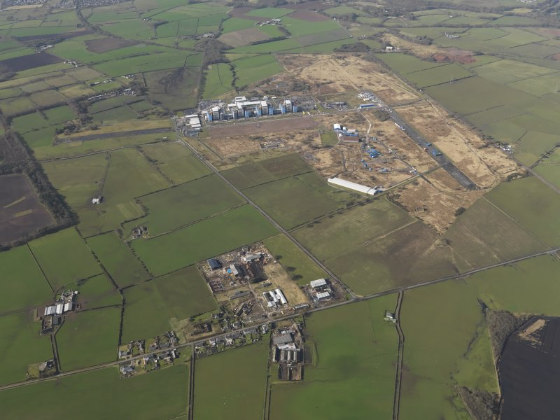 General oblique aerial view centred on the village with the Nuclear power station and airfield adjacent, taken from the ENE.