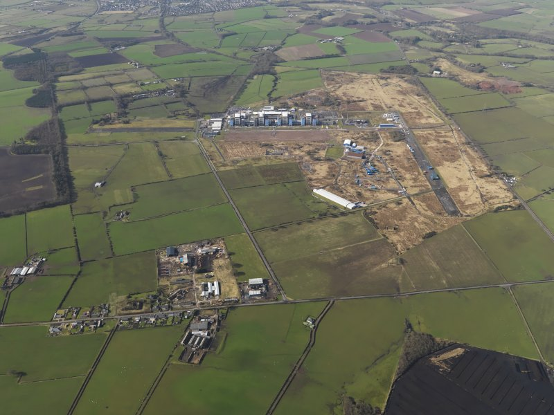 General oblique aerial view centred on the village with the Nuclear power station with the airfield adjacent, taken from the NE.