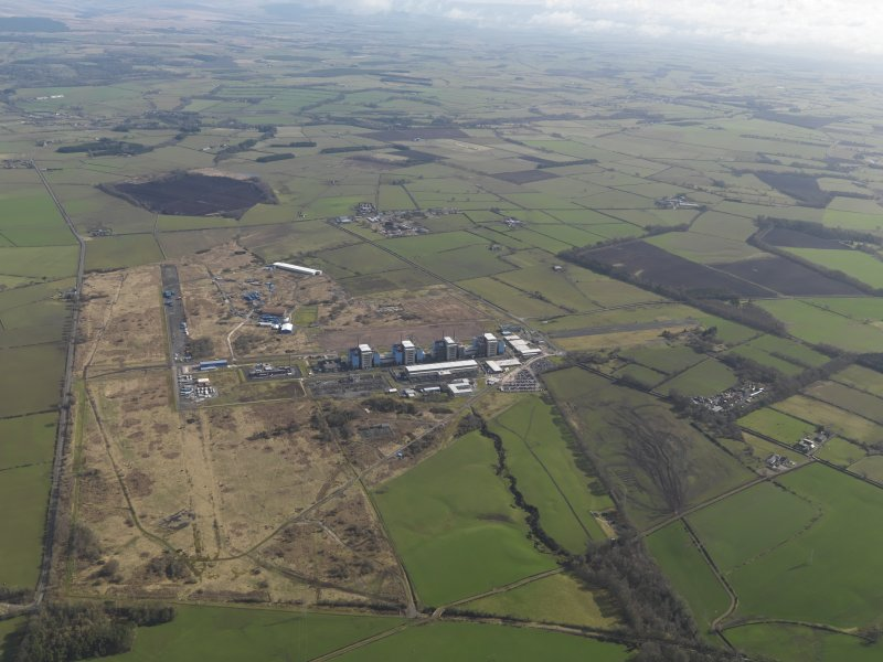 General oblique aerial view centred on the Nuclear power station with the airfield adjacent, taken from the SW.