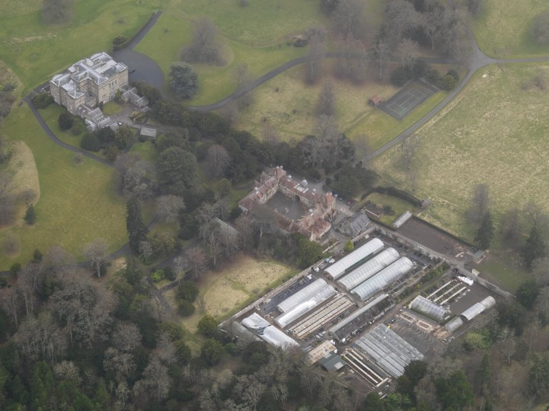 Oblique aerial view centred on the country house with the stables and walled garden adjacent, taken from the N.