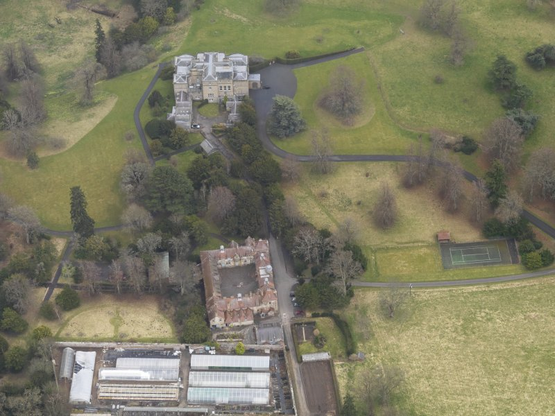 Oblique aerial view centred on the country house with the stables adjacent, taken from the NW.