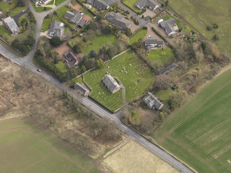 Oblique aerial view centred on the church with the tithe barn adjacent, taken from the NW.