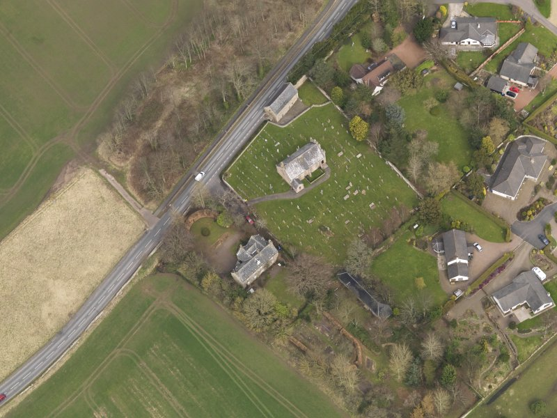 Oblique aerial view centred on the church with the tithe barn adjacent, taken from the SW.