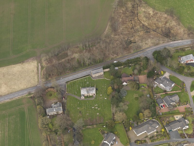 Oblique aerial view centred on the church with the tithe barn adjacent, taken from the SSW.