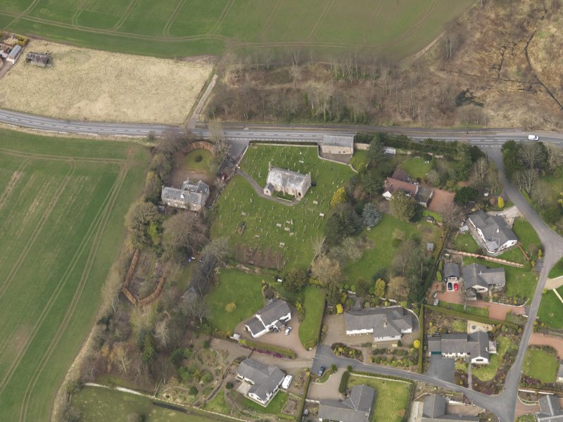 Oblique aerial view centred on the church with the tithe barn adjacent, taken from the S.